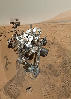 "On Sol 84 (Oct. 31, 2012), NASA's Curiosity rover used the Mars Hand Lens Imager (MAHLI) to capture this set of 55 high-resolution images, which were stitched together to create this full-color self-portrait. The mosaic shows the rover at ""Rocknest,"" the spot in Gale Crater where the mission's first scoop sampling took place"