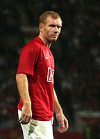 A man with red hair, wearing a red football shirt and white shorts.