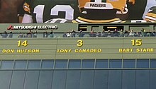 A photo of the retired numbers above the stands at Lambeau Field. Tony Canadeo's #3 is the focus of the image.
