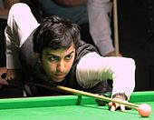 A photograph of a man playing Snooker wearing white shirt and black waistcoat.