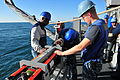 Paul Barnes, left, a contractor, presides over U.S. Sailors assigned to MCM Crew Dominant and deployed aboard the mine countermeasures ship USS Gladiator (MCM 11) as they upgrade a SeaFox portable mine 130117-N-CG436-035.jpg