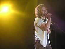 Um cantor masculino, Eddie Vedder, no palco e canta em um microfone vocal.  Ele tem um olhar emocional em seu rosto quando ele canta.