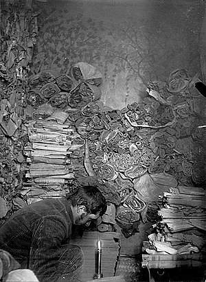 International Dunhuang Project - Paul Pelliot examining manuscripts in the 'Library Cave' (Cave 17) at Dunhuang in 1908
