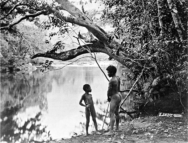 Black and white photograph of a nearly naked man and boy, armed with spears, standing on the bank of a river, under a tree.