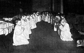 Two rows of little boys, about 20 in total, kneel before their beds in the dormitory of a residential nursery. Their eyes are shut and they are in an attitude of prayer, they wear long white night gowns and behind them are their iron framed beds.
