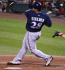 Prince Fielder, wearing the alternate navy-blue Brewers home jersey, in his follow-through after a pitch