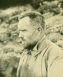 Profile photograph of a man apparently in his thirties, with short dark hair, a neatly trimmed full beard, heavy eyebrows and a high round forehead. He is dressed for outdoor work in cool weather, and is photographed outdoors squinting into the distance.