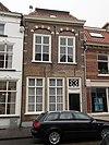 foto van Huis met lijstgevel waarin geprofileerde tooglijsten op maskers plat dak