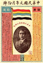 A calendar with a picture of a Chinese man in the middle. On top of it stands a flag with five horizontal stripes (red, yellow, blue, white, and black).