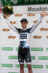 A man in his early twenties wearing a white and black cycling jersey with blue trim and a matching cap. He is holding his arms up in a posture of victory, and holds a bouquet in his right hand.