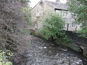 Milnrow - The River Beal flowing through Milnrow, and by its banks, former weavers' cottages. Handloom weaving of woollens was Milnrow's historic staple industry.