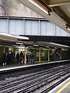Eight people walking towards an escalator on a railway platform next to a green-tiled wall on the left and a railway track on the right