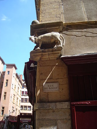 Rue du Bœuf - Plaque of the street and statue of beef, at the corner of the rue and the Place Neuve Saint-Jean.