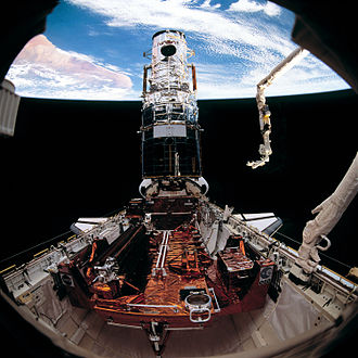 STS-61 - Hubble with new solar arrays installed. The remaining original array is on the SAC in the foreground.