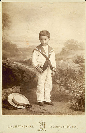 Sailor suit - Photograph of a boy on Oxford Street, Sydney, Australia, wearing a sailor suit, with a sennit straw hat at his feet