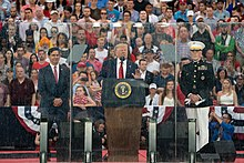 President Trump stands behind a plexiglass shield addressing the crowd. He is flanked by then-Acting Secretary of Defense Mark Esper on the left and Chairman of the Joint Chiefs of Staff Joseph Dunford on the right. A crowd sits on bleachers behind them.