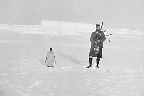 Man on right in Scots highland costume, playing bagpipes, while on the left a lone penguin stands. The ground is covered in ice, with a high ice ridge in the background.