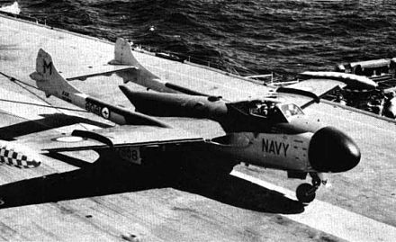 A jet aircraft with a twin tail arrangement sitting on the flight deck of an aircraft carriers. Cables trailing from underneath the aircraft indicate that it has just landed.