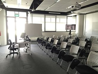 Servicescape - The functional seating, ceiling mounted projectors, whiteboard, fluorescent lighting and schoolroom layout clearly signal that this space is part of an educational environment.