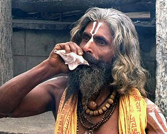 Shankha - A sadhu sounding the shankha.