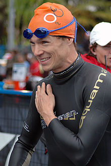 A man wears a black long-sleeved wetsuit, an orange swimming cap, and blue-shaded swimming goggles. He is smiling and holds his left hand over his chest.