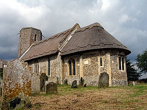 A flint church seen from the southeast, with thatched roofs, an apsidal chancel, a slightly taller nave beyond it, and a tower with an octagonal top