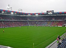 A football match taking place at a sold-out stadium. The sky is cloudy and gray.