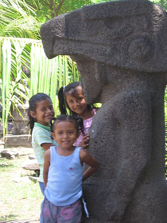 Ometepe - Children standing by a pre-Columbian stone idol.