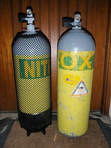 Two cylinders stand next to each other. On the left is a round-bottomed 15-litre steel cylinder with a plastic boot, and on the right a flat-bottomed 12.2-litre aluminium cylinder without boot. Both cylinders are the same outside diameter (203 mm), but the smaller-volume aluminium cylinder is slightly higher than the larger-volume steel cylinder, even though the steel cylinder is standing on a boot and has a rounded bottom.