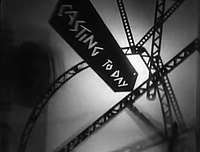 "A series of slanted and curving girders representing an abstract city landscape are set in front of a hazy white backdrop. A slanted black sign appears in the foreground with the words ""CASTING TODAY"" written in jagged white text."