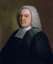 A middle-aged man in black robes with white collar bands and a white wig