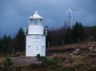 """The old lighthouse at Scoraig (moved to this site and converted to a museum), and in the background a locally designed <a href=""""http://search.lycos.com/web/?_z=0&q=%22wind%20turbine%22"""">wind turbine</a>."""