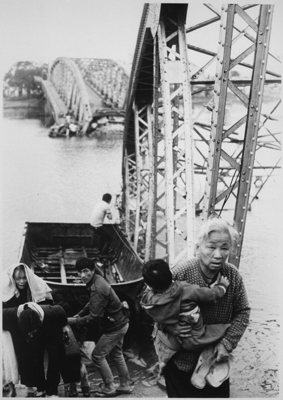 The old and the young flee Tet offensive fighting in Hue, managing to reach the south shore of the Perfume River despite - NARA - 541870