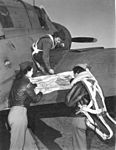 Three WASPs on right wing of A-25 checking the flight plan before a tow mission.JPG