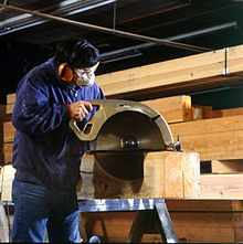 worker uses a large circular saw to cut joints.