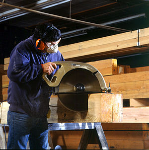 Woodworking joints - A worker uses a large circular saw to cut joints.