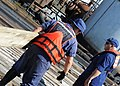 U.S. Coast Guard Petty Officer 3rd Class Matt Roberts, left, moves a board onto an oil platform to conduct cleanup operations in North Barataria Bay near Myrtle Grove, La., Sept 120902-G-TM873-530.jpg