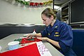U.S. Navy Lt. j.g. Kimberly Robillard, the food service officer aboard the guided missile cruiser USS Monterey (CG 61), decorates her Santa hat on the ship's mess decks Dec. 20, 2013, while underway in 131220-N-QL471-315.jpg