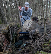 US Army Special Forces MSgt gives instruction to two sniper students