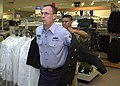 US Navy 030814-N-8861F-007 Master-at-Arms Chief (Select) Scott Kistner, from McClure, Ohio, tries on a Dress Blue jacket at the Navy Exchange uniform store at Naval Station Naples, Italy with the help of Quartermaster Chief Atl.jpg