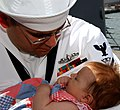 US Navy 040527-N-7631T-037 Fire Controlman 2nd Class Mathew Bergoschije embraces his new daughter Hannah during homecoming celebrations.jpg
