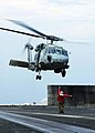 US Navy 050104-N-6074Y-016 A Landing Signals Enlisted (LSE) Sailor launches a SH-60F Seahawk helicopter off the flight deck of USS Abraham Lincoln (CVN 72) en route to Aceh, Sumatra, Indonesia carrying relief supplies.jpg