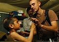 US Navy 051101-N-1261P-029 U.S. Army 1st Lt. Tory Marcon, assigned to the 212th MASH unit, helps a Pakistani child drink a powered milkshake from a Meals Ready-to-Eat (MRE) in Muzaffarabad, Pakistan.jpg