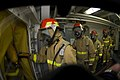 US Navy 070726-N-9864S-005 Hose team members enter a smoke boundary to combat a simulated fire during a general quarters drill aboard USS Kitty Hawk (CV 63).jpg