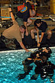 US Navy 070908-N-1159B-041 Navy Diver 1st Class Paul Ford, Information Systems Technician 1st Class Stephen Moretti, Machinist's Mate 1st Class Christopher Lidh and Lt. Cmdr. Brian assist Cmdr. James Bates who is acting as an u.jpg