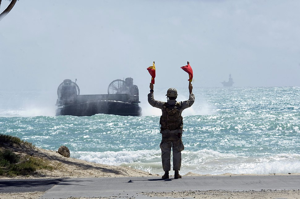 US Navy 080722-N-6270R-066 Boatswain's Mate 2nd Class Derrick Riley uses signal flags to guide a landing craft air cushion
