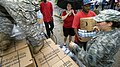 US Navy 080903-N-6266K-038 Army National Guard Spc. Jacquelyn Smith hands out bottles of water and boxes of meals ready to eat.jpg