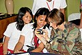 US Navy 091009-N-1008D-076 Lt. Lara Bollinger, deputy public affairs officer for Joint Special Operations Task Force-Philippines (JSOTF-P), instructs two photojournalism students on basic camera settings.jpg