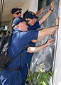 US Navy 091026-N-6692A-050 Sailors assigned to the dock landing ship USS Tortuga (LSD 46) replace a protective window screen at Kalalake Elementary School during a community service project.jpg