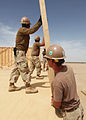 US Navy 100428-M-3256G-002 Seabees assigned to Detail Delaram II from Naval Mobile Construction Battalion (NMCB) 133, raise the walls during the construction of a Southwest Asia hut on a forward operating base in Delaram, Afgh.jpg